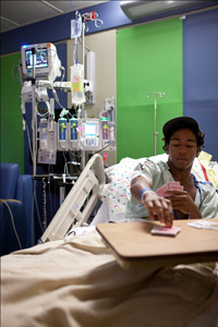 patient playing cards while laying in bed, an example of palliative care