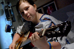 girl playing a guitar while wearing a hospital gown, an example of palliative care